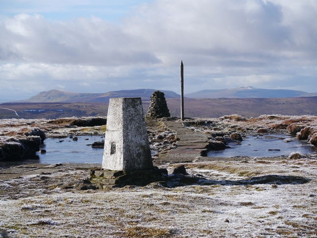 The trig point, cairn and stake on the summit of Buckden Pike