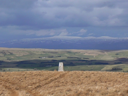 The trig point on Middleton with the snow capped Cross Fell and the two Dun Fells in the distance